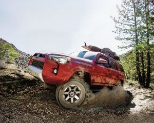 4Runner TRD Off Road in red driving over a rough landscape