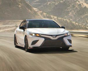 2020 Toyota Camry TRD in white driving fast in a hilly section