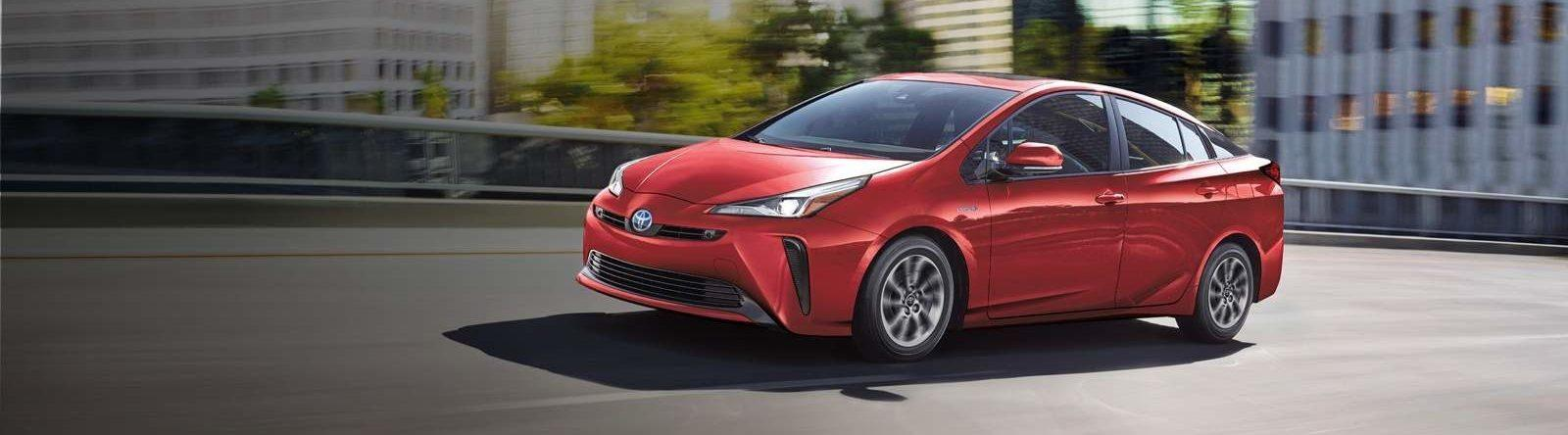 Side front view of 2021 Toyota Prius Technology in supersonic red driving on a city road