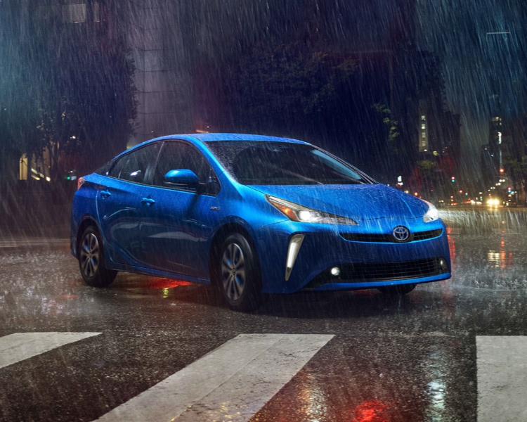2021 Toyota Prius AWD-e in electric storm blue parked in the middle of the street while it's raining