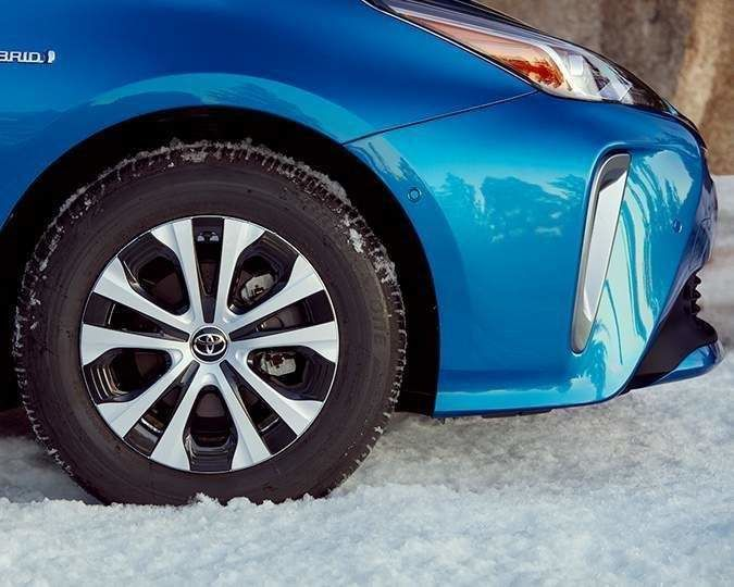 Side view close-up of front right Toyota Prius wheel on snow