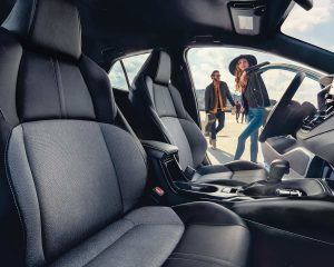 2021 Toyota Corolla Hatchback side view interior with a man and a woman standing outside