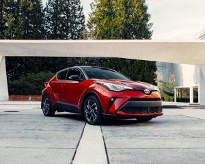 2021 Toyota C-HR Limited in Supersonic Red with black root, parked in front of a small bridge on a building