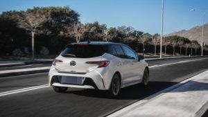 Rear of white Toyota Corolla hatchback driving with trees lining the road