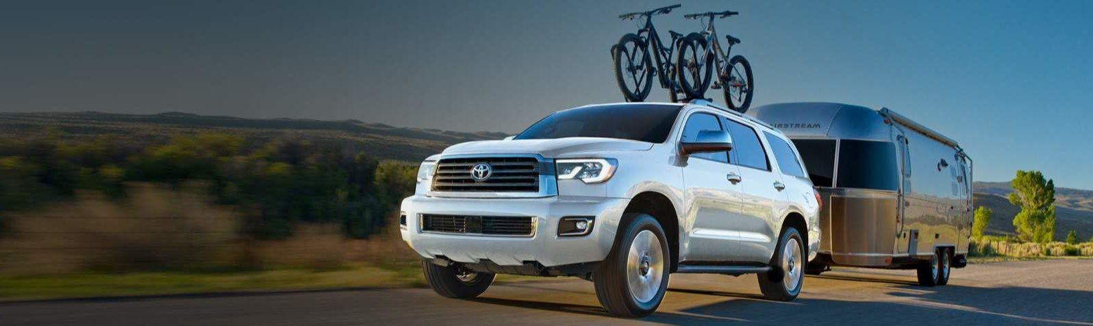 2021 Toyota Sequoia with a bikes on top and pulling a trailer